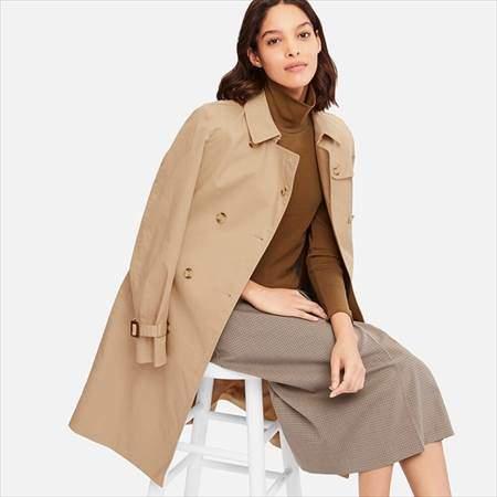 ユニクロのトレンチコートのベージュを着ている女性